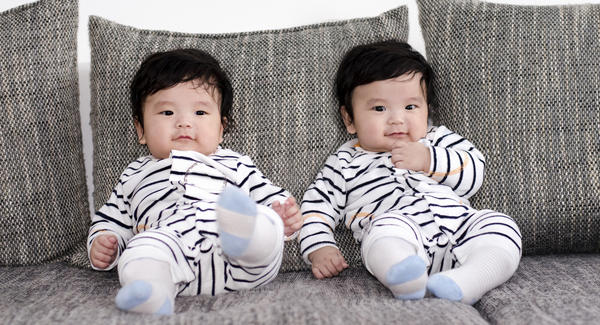 twin babies sitting on a couch